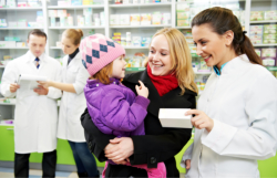 A mother carrying her daughter while talking to a pharmacist